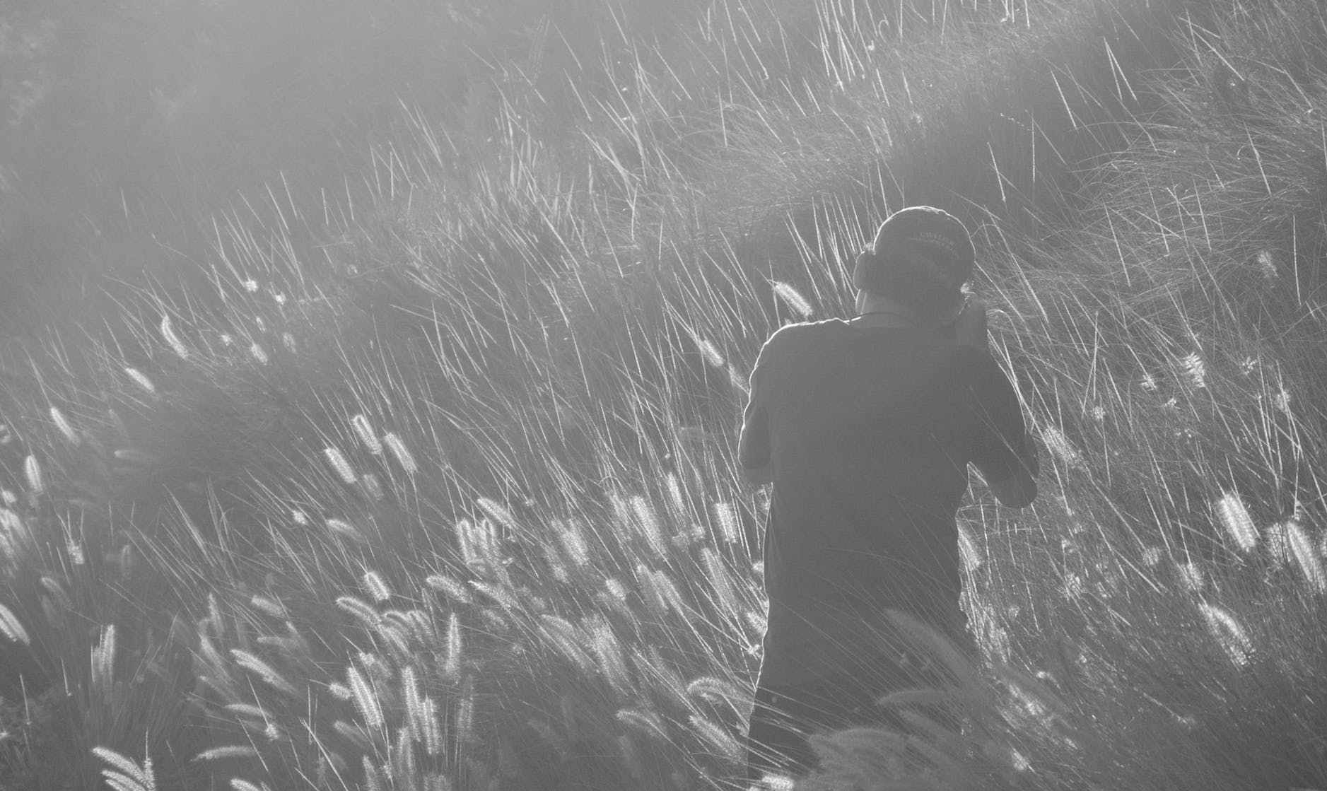 man taking photo on grass field in greyscale photography